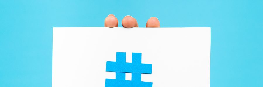 Hand showing hashtag notification concept on blue background