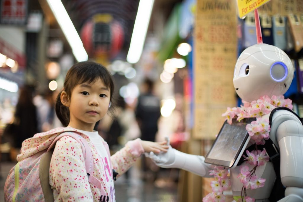 Girl holding the hand of a robot